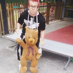 A photograph of a man with pink hair and glasses. He is wearing a black suit with a skeleton on it. He has a teddy bear attached to him by pieces of fabric. His wrists are linked to the Teddy's wrists, his ankles to the Teddy's ankles and a piece of fabric loops round his neck to support the Teddy's head.
