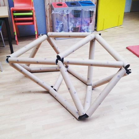 [photo shows a sculpture made up of large cardboard tubes. It's held together by elastic running through the tubes. It's a geometric structure with a lot of triangles making up its shape]