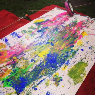 A photograph showing a large sheet of paper on the ground covered in different colours of paint. There is a small tyre in the corner with a bamboo pole through the centre which extends either side of the tyre to cover the width of the paper. The tyre is also covered in paint as it has been used to make marks on the paper