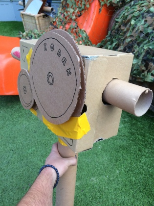 """Photo of a Camera made from a cardboard box, some cardboard tubes and cardboard reels with """"Kodak"""" written on them. Its held together with bright yellow duct tape. Its pretty damn cool"""