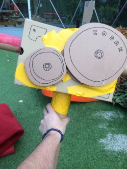 "Photo of a hand holding out a cardboard film camera, it has a long cardboard tube ""lens"" sticking out of the side and two cardboard reels attached with yellow duct tape."