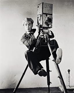 """Photo of silent-movie actor Buster Keaton dressed as """"the cameraman"""". He is dressed n a shabby suit, bow tie and cap and is clinging to the tripod of his camera, legs off the ground looking stone faced into the distance."""