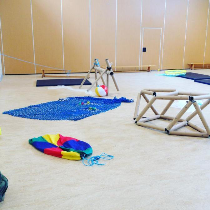 [photo shows a bare gym hall which has been filled with a variety of structures, mats and balls. They are set up in a temporary way to allow anyone to come in a explore and play. There are two different cardboard tube structures, a blue net with small coloured balls under it, a beach ball, and colourful parachute]