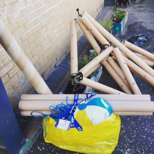 [photo shows a collection of objects on the pavement next to a building. There is a large structure made of cardboard tubes. Several loose tubes of varying sizes and a bright yellow bag with a beach ball poking out of the top}
