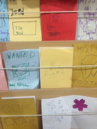 Image shows a close up of a leaflet stand with colourful hand drawn leaflets. One is a blue wanted poster which says 'oof' underneath, one is yellow with a pencil drawing of a robot and one is gold with a large tooth drawn in the middle and the headline 'missing tooth'