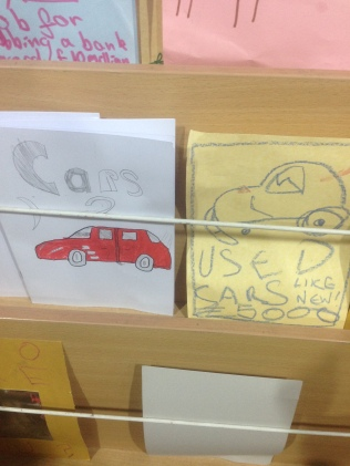 Image shows close up of two leaflets in a leaflet stand, one says 'Cars 2' and has a drawing of a red car and the second says Used cars, like new, £5000 with a drawing of a very old damaged looking car.