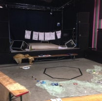 Image is a photograph taken from the back of a space looking towards a stage. The stage has a washing line across it with 6 large sheets of paper attached. In front of the stage is a bench. In front of the bench on the floor is a heptagon marked out by black tape. Laying around the shape are several pieces of fabric and objects including masks, toy cars and bouncy balls.